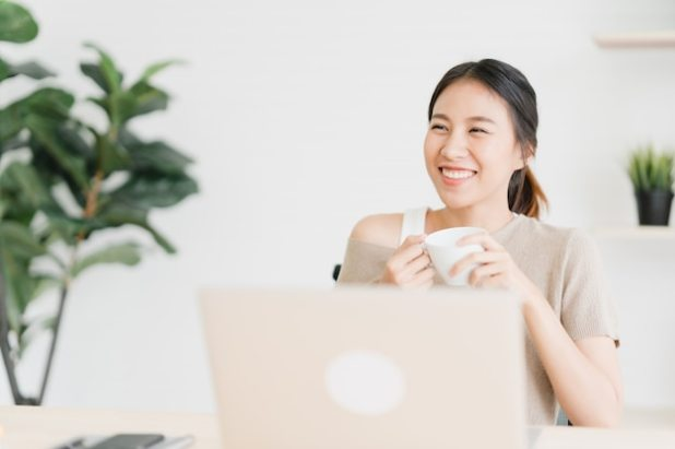 Beautiful young smiling asian woman working on laptop and drinking coffee Free Photo