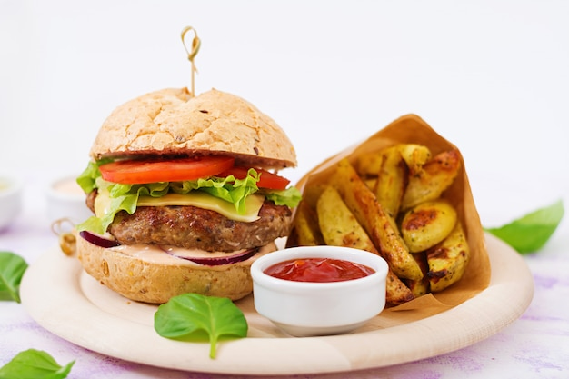 Big sandwich - hamburger with juicy beef burger, cheese, tomato, and red onion and french fries. Free Photo