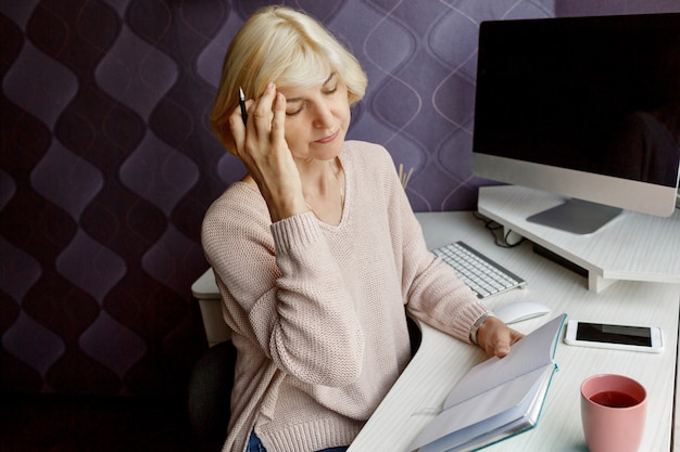 Blond Mature Woman Writing In Her Planner While Working By