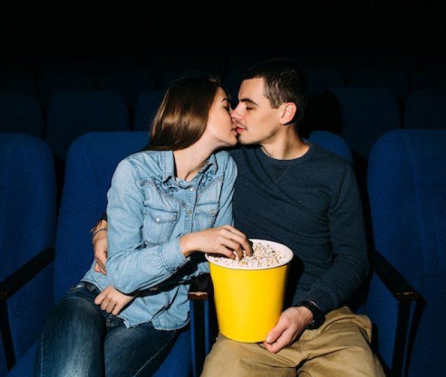 Young Beautiful Couple Kissing While Watching Romantic Movie At Cinema Free Photo