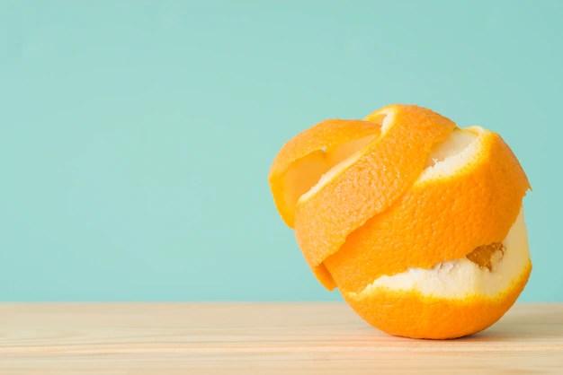 Close-up of a peeled orange fruit on wooden surface Free Photo