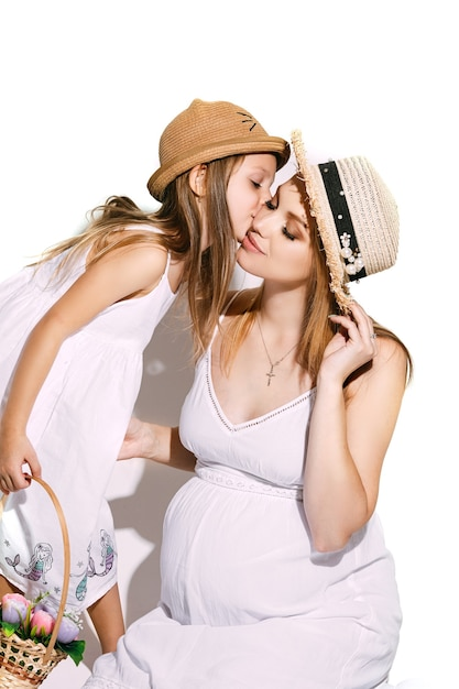 Cute girl with a basket of flowers leaning towards the mother and kissing her cheek. Free Photo