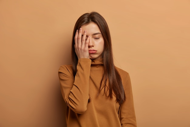 Distressed fatigue woman covers face with palm, feels bored and tired, wants sleep after all night exam preparation, needs rest or support Free Photo