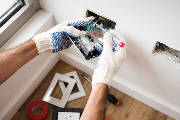 Electrician's hand installing power socket at home Premium Photo