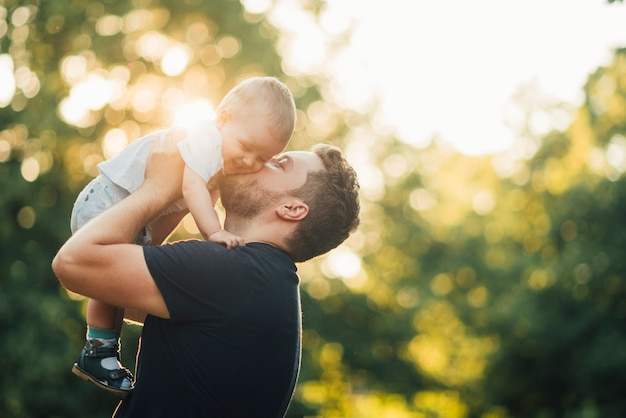 Father kissing his baby in the park Free Photo