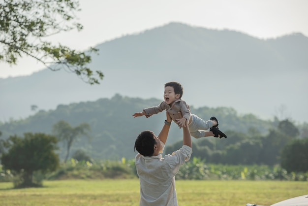 Father and son playing in the park at the sunset time. people having fun on the field. concept of friendly family and of summer vacation. Free Photo