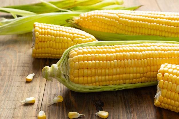 Fresh corn on wooden table. Free Photo