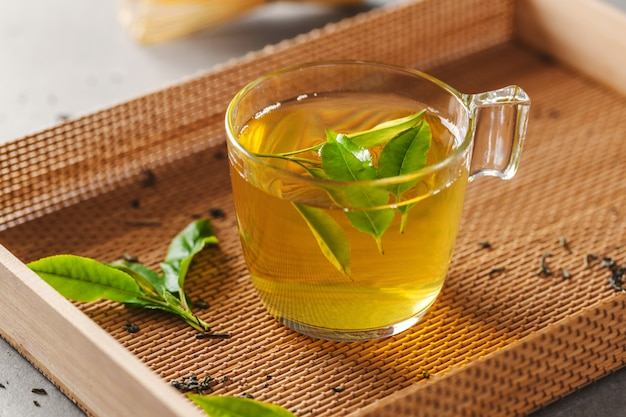 Green tea brewed in cup with tea leaves on table. closeup. Premium Photo
