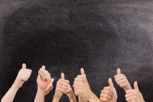 Hands with thumbs up gesture against a blackboard Free Photo