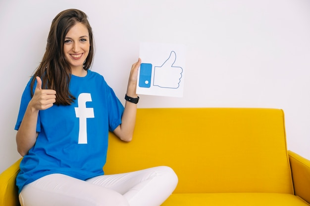 Happy woman sitting on sofa holding like icon showing thumb up sign Free Photo