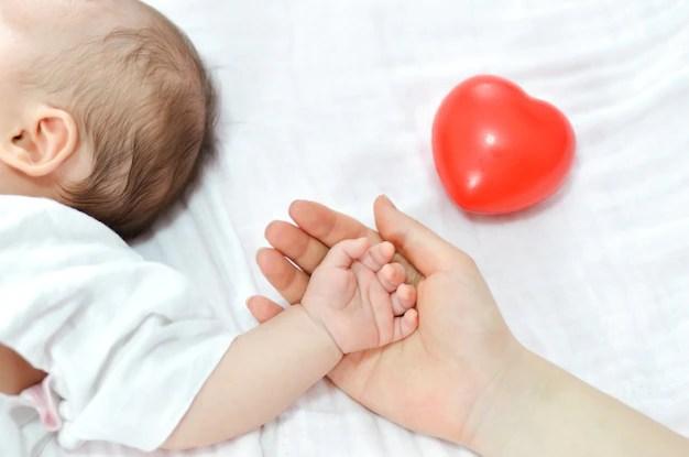 Mãe segurando mão de bebe deitado em lençol branco peso ideal