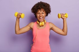 Horizontal shot of energized happy afro woman raises arms with dumbbells, enjoys sport training with music in headphones, dressed in casual pink vest, poses indoor. people Free Photo