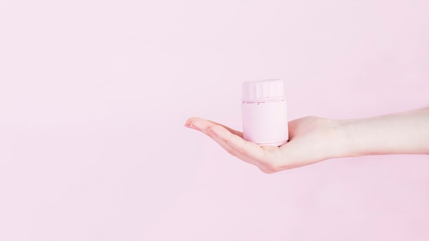 Human hand with bottle for medicine pills over pink background Free Photo