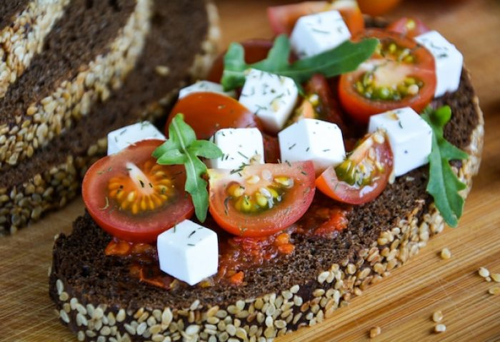 Juicy Sandwich With Tomato Cheese And Herbs On Black Bread With