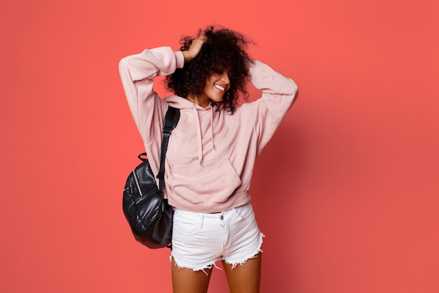 Free Photo | Lovely sexy black woman in stylish hoodie with back pack  posing on pink background and playing with curly hairs.