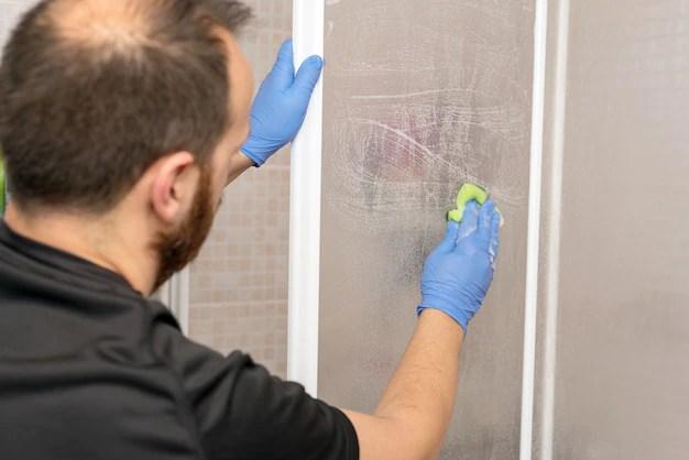 Man cleaning shower cabin. Premium Photo