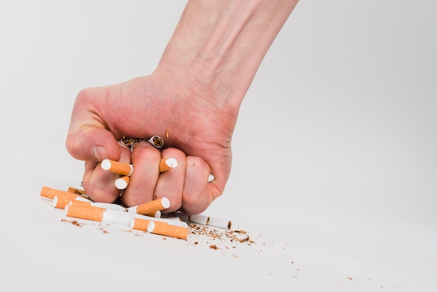 A man's fist crushing cigarettes over white background Free Photo