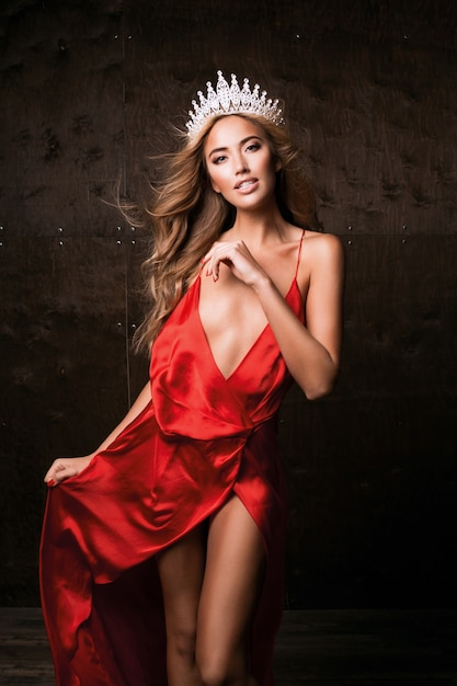 Miss universe wearing long silk red dress and crown. natural makeup, curly hairstyle Free Photo