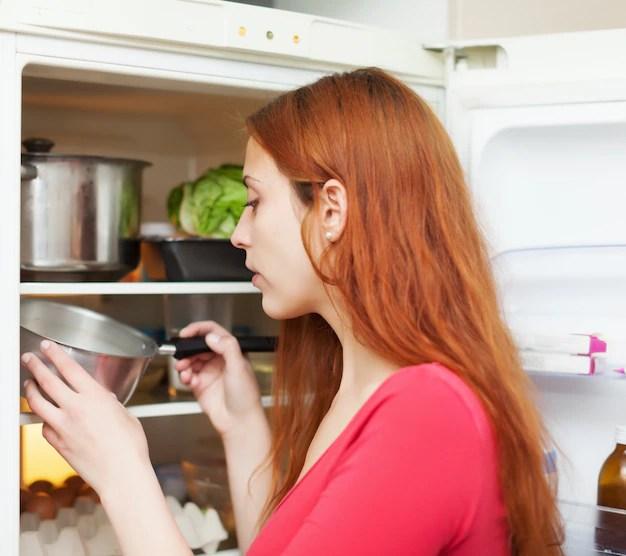 冷蔵庫で何かを探している赤毛の女性 無料写真
