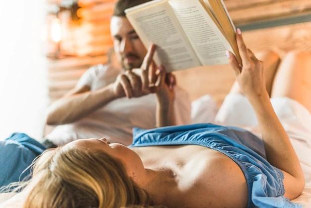 読書のベッドに横たわっている彼女の妻を見ている男 無料写真