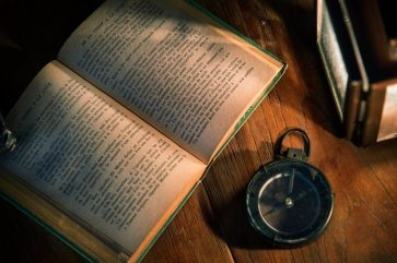 An old book on a wooden table Free Photo - ways to find inspiration for your next song