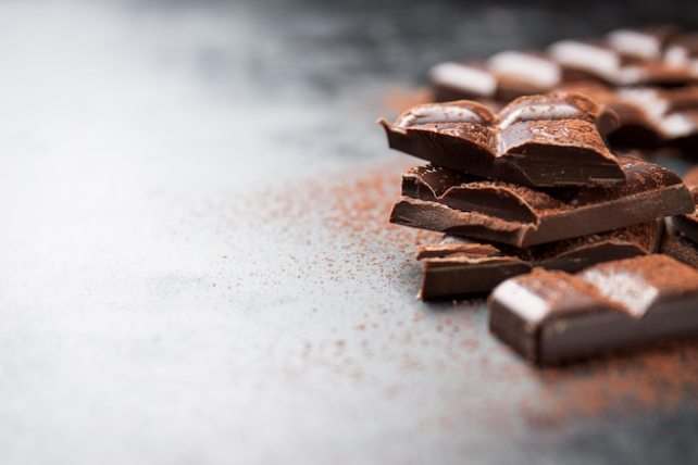 Pieces of chocolate on a wooden table and cacao sprinkled Free Photo