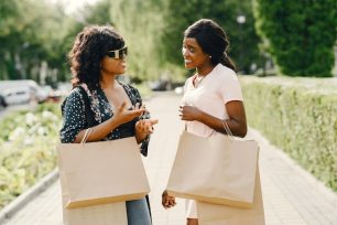 Portrait of beautiful young black women with shopping bags Free Photo