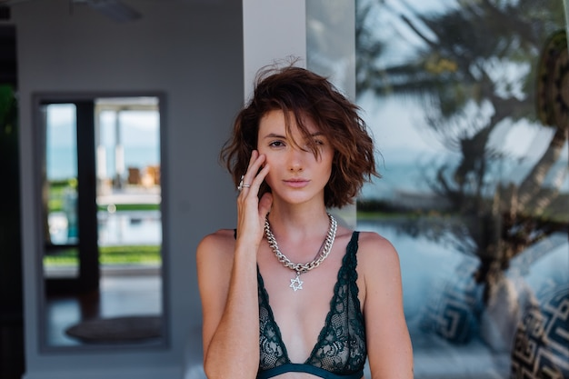 Portrait of short hair brunette woman with chain on neck accessories in green lace lingerie outside villa Free Photo
