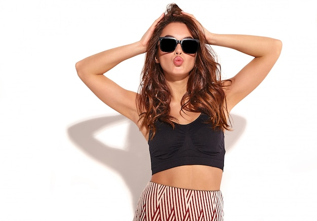Portrait of young stylish girl model in casual summer clothes with natural makeup in sunglasses isolated. giving air kiss Free Photo