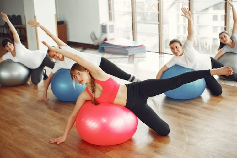 Pregnant women doing yoga with a coach Free Photo