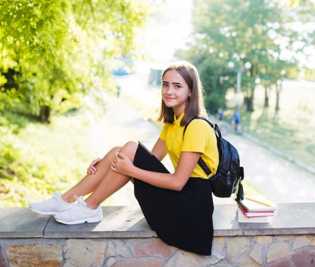 Pretty Teen Girl Sitting On Fence Free Photo