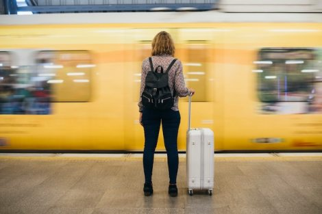 Rear view of a blond woman waiting at the train platform Free Photo