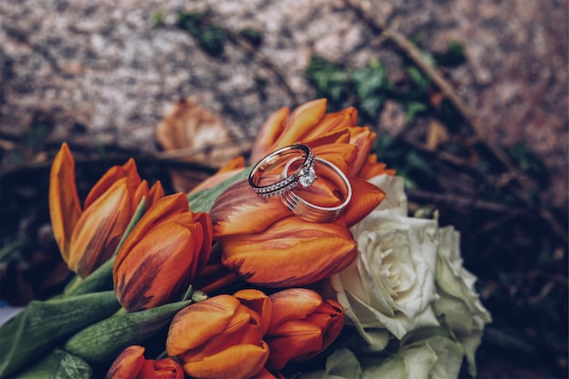 Selective closeup shot of silver diamond rings on orange tulips and white roses Free Photo