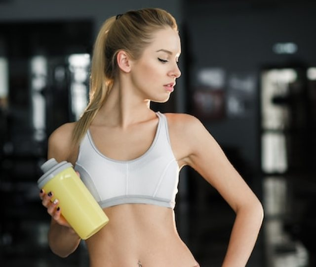 Sexy Woman With Yellow Bottle At The Gym Free Photo