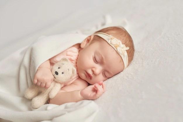 Bebê menina de 3 meses dormindo abraçada em ursinho peso ideal