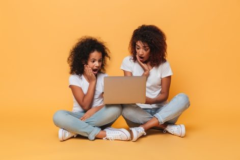 Two surprised afro american sisters using laptop computer Free Photo