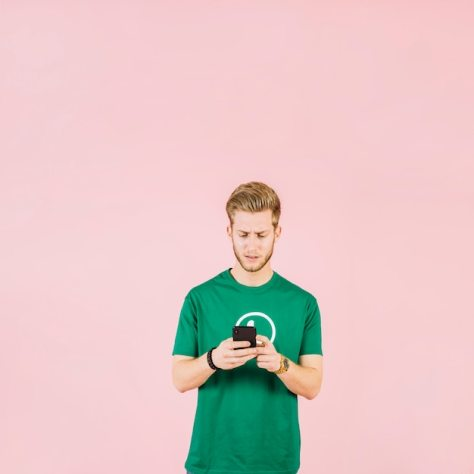 Upset young man using mobile phone over pink background Free Photo
