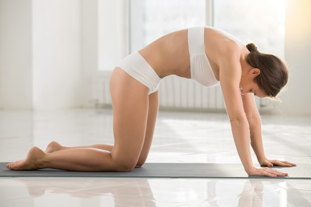Young attractive woman standing in Marjaryasana pose, white colo Free Photo