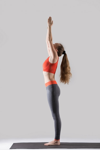 Young attractive woman standing in Tadasana pose, grey studio ba Free Photo