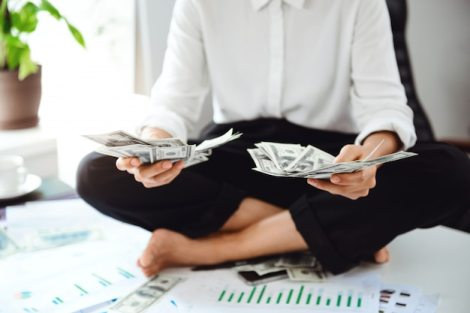 Young beautiful businesswoman holding money, sitting on table at workplace. Free Photo