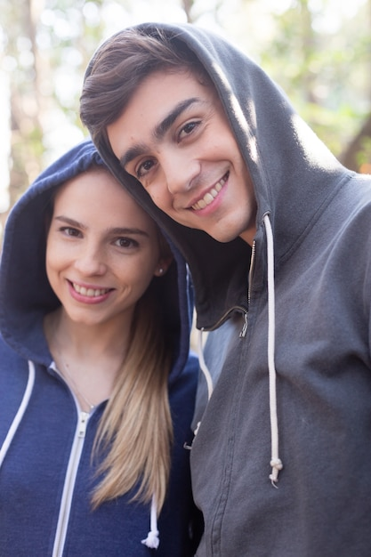 Young Couple With A Big Smile Wearing Hooded Sweatshirts