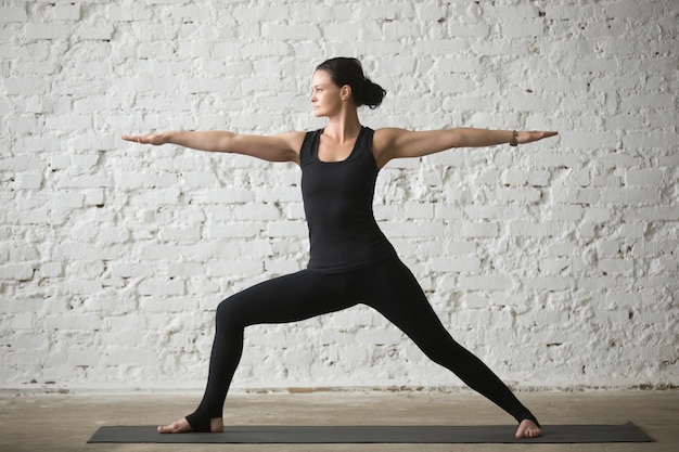 Young yogi attractive woman in Warrior Two pose, loft background Free Photo