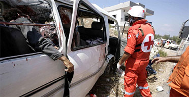 Red Cross workers arrive at the scene of an Israeli air attack which killed three members of one family, including a grandmother, and injured 16 others. Photograph: Sean Smith/Guardian