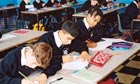 School pupils writing at desks