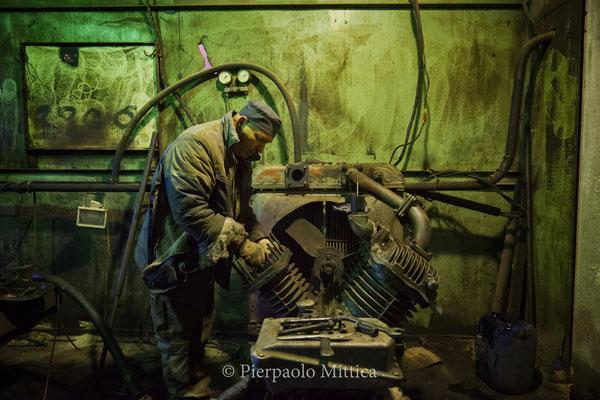 Pavel mentre ripara il motore del sistema di ventilazione all'interno del magazzino per il riciclo dei metalli radioattivi