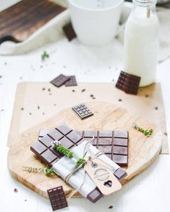 Zuckerfreie Schokolade von oben fotografiert. Im Hintergrund steht eine Flasche Milch.