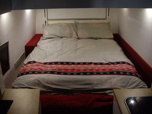 The bed with its raising mechanism visible at the far end