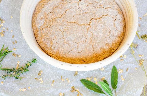 Das ist das Bild von 10 Tipps beim Brot backen. Auf dem Bild ist ein Gärkörbchen mit einem Brotteig zu sehen. Daneben liegt frisches Getreide und Kräuter.