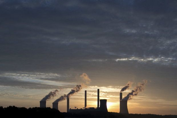 In this June 3, 2017, file photo, the coal-fired Plant Scherer, one of the nation's top carbon dioxide emitters, stands in the distance in Juliette, Ga. A recent poll finds that less than a third of Americans support President Donald Trump's decision to withdraw from the Paris climate accord, with just 18 percent of respondents agreeing with his claim that pulling out of the international agreement to reduce carbon emissions will help the U.S. economy.(AP Photo/Branden Camp, File)