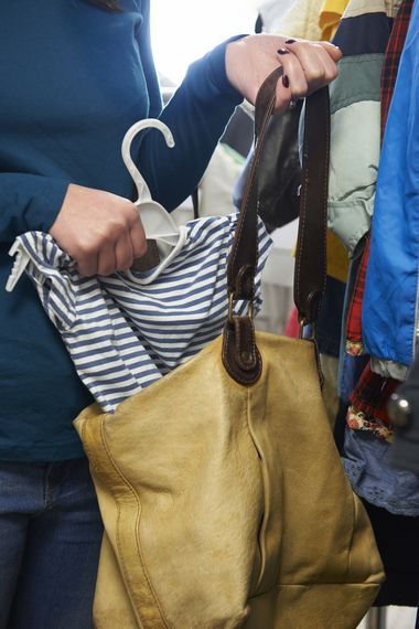A woman placing a shirt on a hanger into her bag